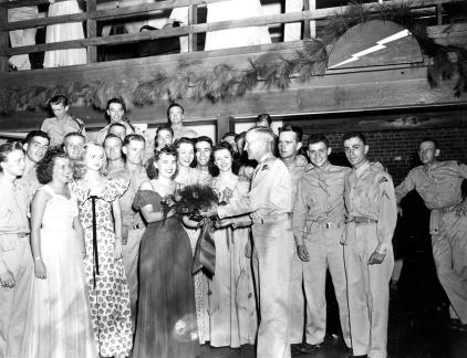 """Presentation of flowers to beauty queen at Service Club #2, Camp Butner, N.C."""
